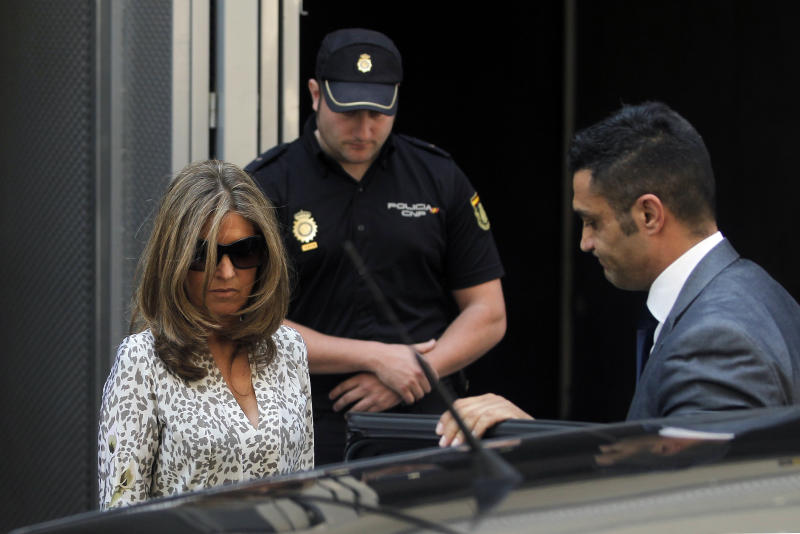 Rosalía Iglesias Villar, right, wife of the former Popular Party treasurer, Luis Barcenas, unseen, leaves the National Court in Madrid, Spain, Thursday, June 27, 2013. A judge has ordered that Barcenas be held in jail while he awaits trial on charges of tax fraud and money laundering.(AP Photo/Andres Kudacki)