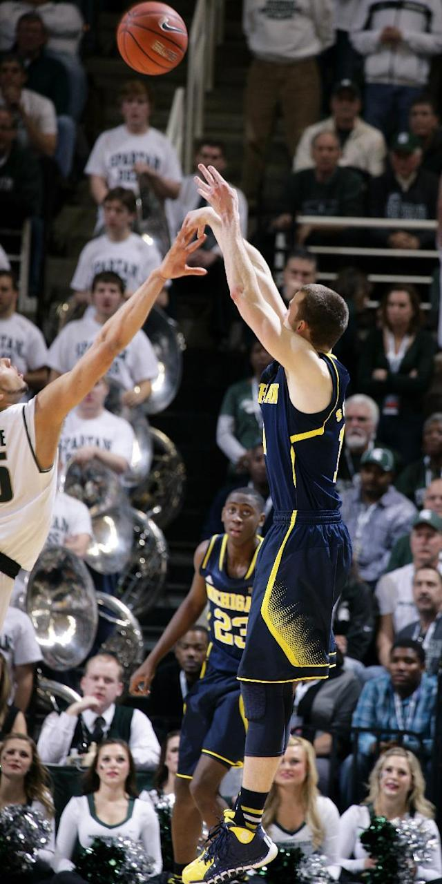 Michigan's Nik Stauskas, right, makes a 3-pointer against Michigan State's Denzel Valentine, left, to break a tie and put Michigan up for good late in the second half of an NCAA college basketball game, Saturday, Jan. 25, 2014, in East Lansing, Mich. Michigan won 80-75. (AP Photo/Al Goldis)