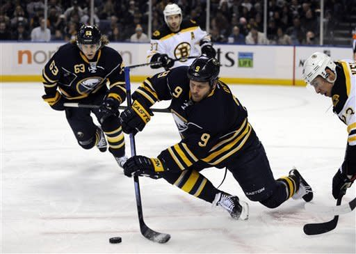 Buffalo Sabres' center Steve Ott (9) dives to pass the puck on a face-off against Boston Bruins center Chris Kelly (23) as Sabres Tyler Ennis (63) and Bruins' Patrice Bergeron (37) look on during the first period of an NHL hockey game in Buffalo, N.Y., Friday, Feb. 15, 2013. (AP Photo/Gary Wiepert)