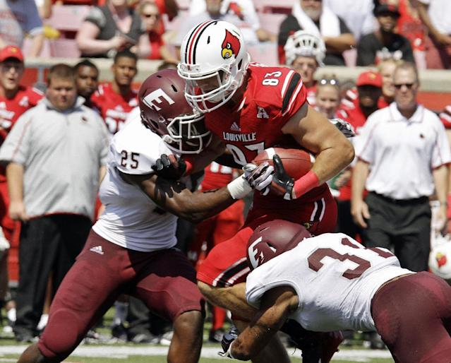 Louisville tight end Ryan Hubbell (83) gets hit from both sides by Eastern Kentucky tacklers Chris Owens (25) and Christian Albertson (31) after this pass catch in the first quarter of their NCAA college football game in Louisville, Ky., Saturday, Sept. 7, 2013. (AP Photo/Garry Jones)