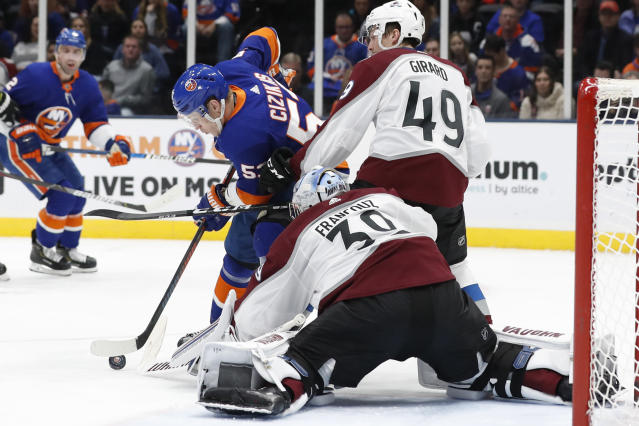 Colorado Avalanche defenseman Samuel Girard (49) defends New York Islanders center Casey Cizikas (53) who tries to maneuver the puck in front of Avalanche goaltender Pavel Francouz (39) during the second period of an NHL hockey game, Monday, Jan. 6, 2020, in Uniondale, N.Y. (AP Photo/Kathy Willens)