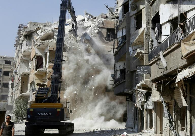 A demolition excavator works on a multi-storey building in Harasta, which Syria's government captured in March after a blistering weeks-long assault