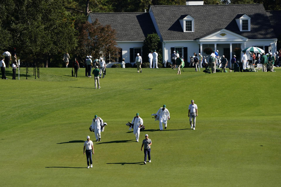 Golfers and caddies walk up the first fairway during the second round of the Masters golf tournament Friday, Nov. 13, 2020, in Augusta, Ga. (AP Photo/Matt Slocum)