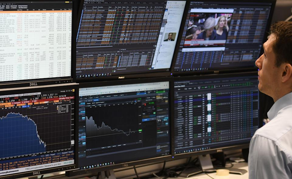 A trader looks at screens of financial data