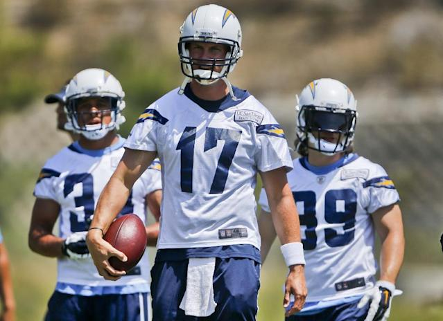 San Diego Chargers quarterback Philip Rivers leads some of his offensive teammates to a drill during an NFL football organized team activity Monday, June 9, 2014, in San Diego. (AP Photo/Lenny Ignelzi)