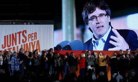 Ousted Catalan leader Carles Puigdemont appears on a screen during an event of his political platform