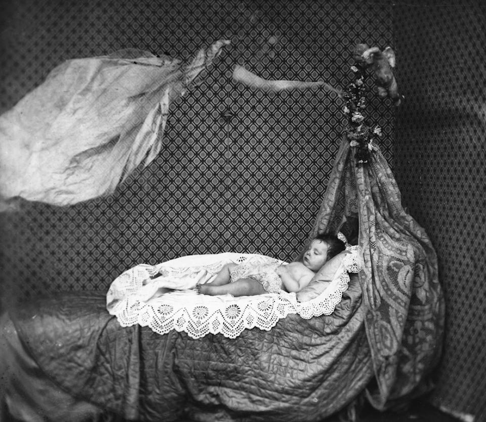 """<p>In another example of spirit photography, a long-haired woman floats above a baby's bed. According to <em>BBC</em>, the most famous case of double-exposure spirit photography <a href=""""https://www.bbc.com/future/article/20150629-the-intriguing-history-of-ghost-photography"""" rel=""""nofollow noopener"""" target=""""_blank"""" data-ylk=""""slk:involves a portrait of Mary Todd Lincoln"""" class=""""link rapid-noclick-resp"""">involves a portrait of Mary Todd Lincoln</a>, which features a ghostly Abraham Lincoln standing right behind her. </p>"""