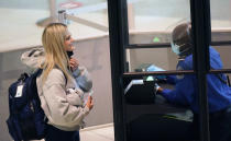 A traveler smiles as they pull down their mask for a TSA agent to confirm their identity at the security checkpoint at Love Field airport Friday, May 28, 2021, in Dallas. (AP Photo/LM Otero)