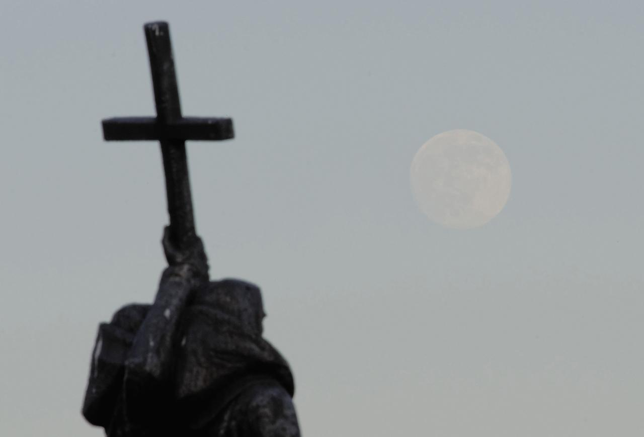 "The moon rises over the monument of Saints Cyril and Methodius, the fathers of Slavonic literature, in the Russian far eastern city of Vladivostok June 22, 2013. On Saturday a perigee moon will coincide with a full moon creating a ""super moon"" when it will pass by the earth at its closest point in 2013 REUTERS/Yuri Maltsev (RUSSIA - Tags: ENVIRONMENT SCIENCE TECHNOLOGY SOCIETY)"