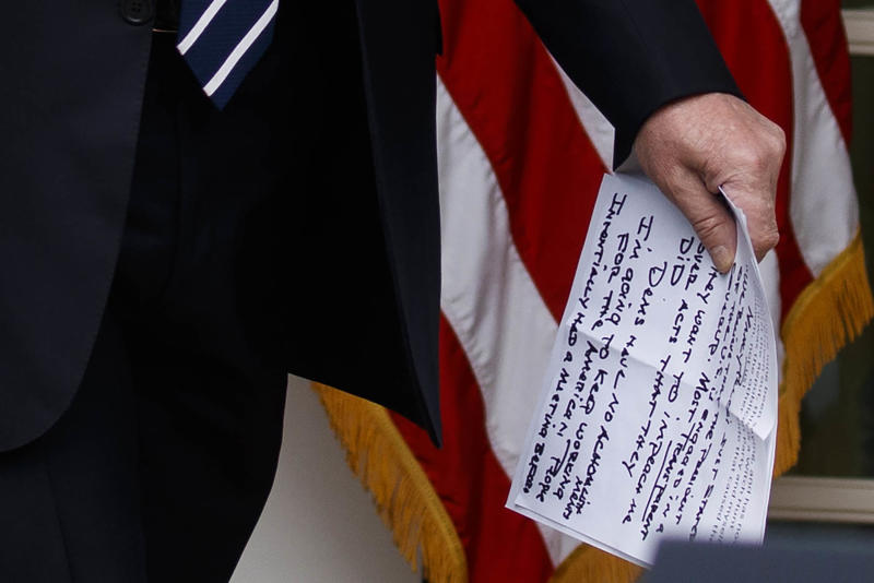 Trump carries notes that say