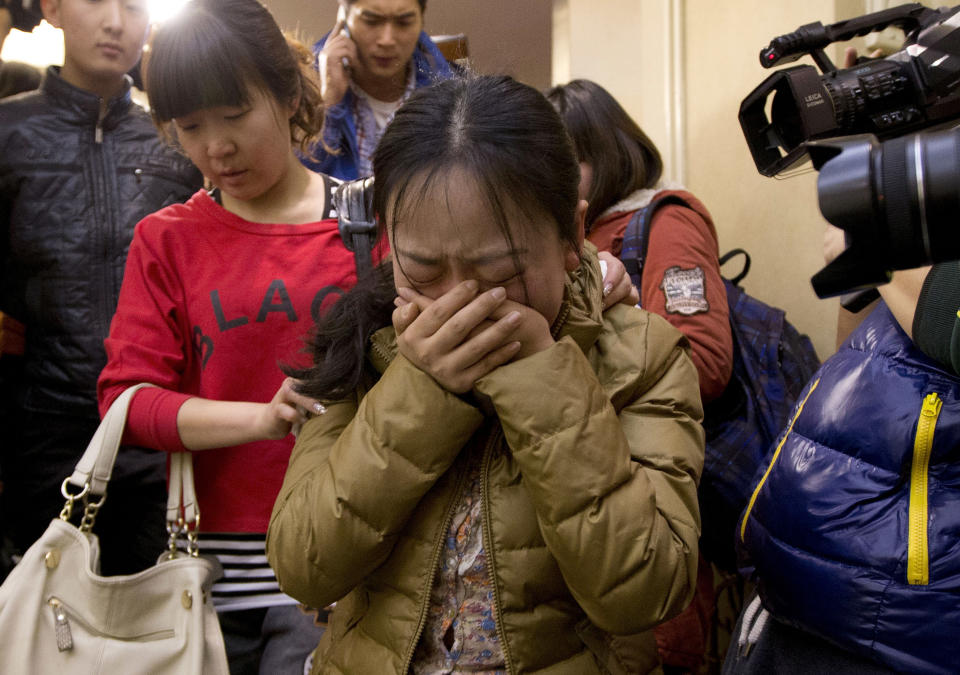 <p> A Chinese relative of passengers aboard a missing Malaysia Airlines plane, center, cries as she is escorted by a woman while leaving a hotel room for relatives or friends of passengers aboard the missing airplane, in Beijing, China Sunday, March 9, 2014. Planes and ships from across Asia resumed the hunt Sunday for the Malaysian jetliner missing with 239 people on board for more than 24 hours, while Malaysian aviation authorities investigated how two passengers were apparently able to get on the aircraft using stolen passports. (AP Photo/Andy Wong) </p>