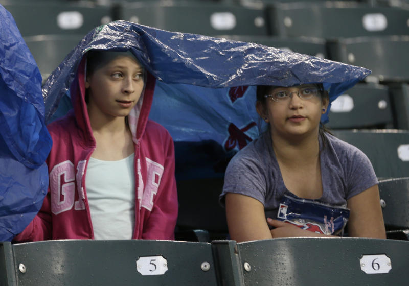 Lydia Obman, left, and Isabelle Seewald stay covered as they wait out a rain delay before a baseball game between the Cleveland Indians and the Tampa Bay Rays, Friday, May 31, 2013, in Cleveland. (AP Photo/Tony Dejak)
