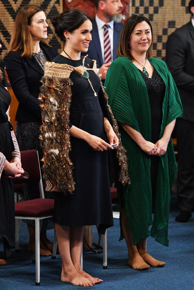 """<p>For the moving proceedings Meghan wore her hair in her signature chignon, with the <a href=""""https://www.net-a-porter.com/gb/en/Shop/Designers/Stella_McCartney?cm_mmc=GoogleUK--c-_-NAP_EN_UK_London-_-NAP+-+INTL+-+London+-+Designer_Stella+McCartney+-+BT--Stella+McCartney+-+Alone+-+Exact-_-stella+mccartney_e_kwd-143705115_INTL&gclid=EAIaIQobChMI0uX2kcuw3gIV6LDtCh1logEcEAAYASAAEgKWPfD_BwE&gclsrc=aw.ds&pn=1&npp=60&image_view=product&dScroll=0"""" rel=""""nofollow noopener"""" target=""""_blank"""" data-ylk=""""slk:Stella McCartney"""" class=""""link rapid-noclick-resp"""">Stella McCartney</a> Cady Crepe dress in midnight blue, a traditional necklace and her repeated navy Manolo Blank BB stilettos.</p>"""