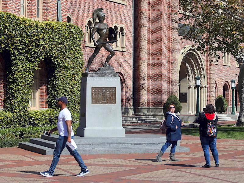 FILE - In this March 12, 2019 file photo, people pose for photos in front of the iconic Tommy Trojan statue on the campus of the University of Southern California in Los Angeles. USC will phase in free tuition for students from families with an annual income of $80,000 or less, USC President Carol L. Folt announced Thursday, Feb. 20, 2020. As part of the initiative, ownership of a home will not be counted in determining a student's financial need. (AP Photo/Reed Saxon, File)