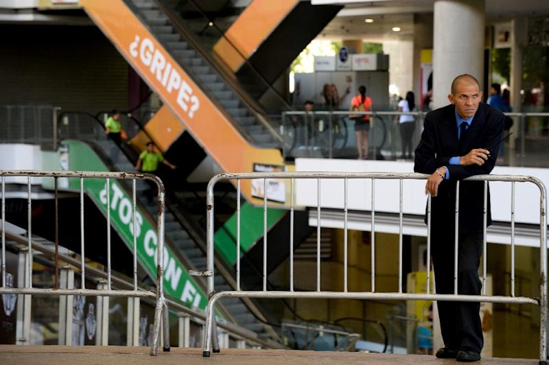 A security guard waits at the entrance of a shopping centre closed in Caracas on February 10, 2016 (AFP Photo/Federico Parra)