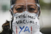 "A healthcare worker, wearing a protective face mask with a message that reads in Spanish: ""We demand vaccines now!"", attends a march demanding a more equitable and faster distribution of COVID-19 vaccines, in the Los Palos Grandes neighborhood of Caracas, Venezuela, Saturday, April 17, 2021. (AP Photo/Matias Delacroix)"