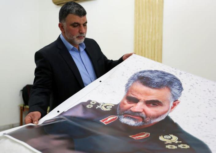FILE PHOTO: A man holds a banner depicting late Major-General Qassem Soleimani, head of the elite Quds Force, who was killed in a U.S. airstrike Near Baghdad, at the Iranian embassy in Beirut