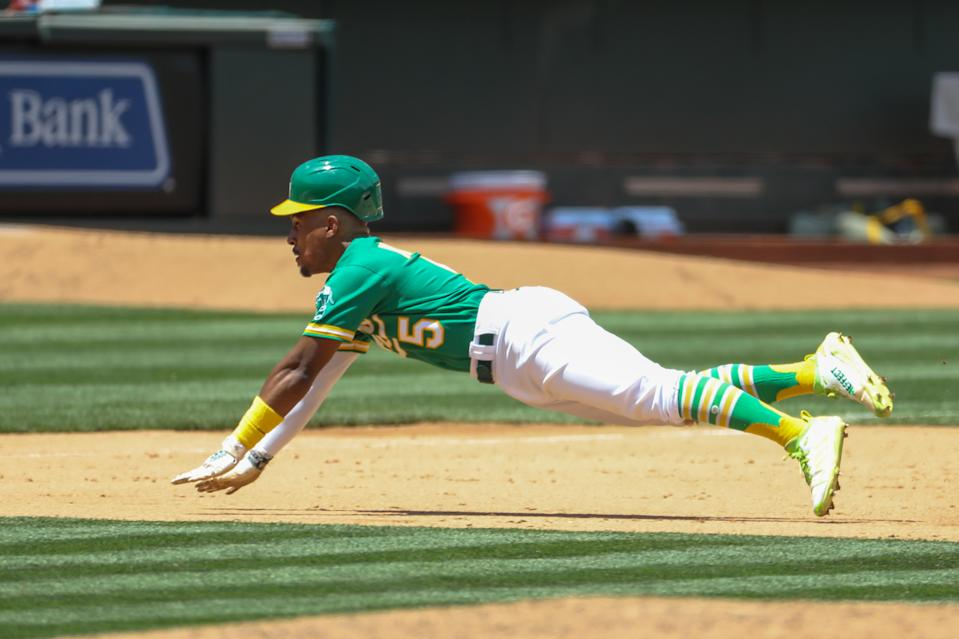 OAKLAND, CA - JUNE 16: Oakland Athletics second baseman  Tony Kemp (5) slides into third base during the MLB game between the Los Angeles Angels and the Oakland Athletics on June 16, 2021, at RingCentral Coliseum in Oakland, CA. (Photo by Kiyoshi Mio/Icon Sportswire via Getty Images)