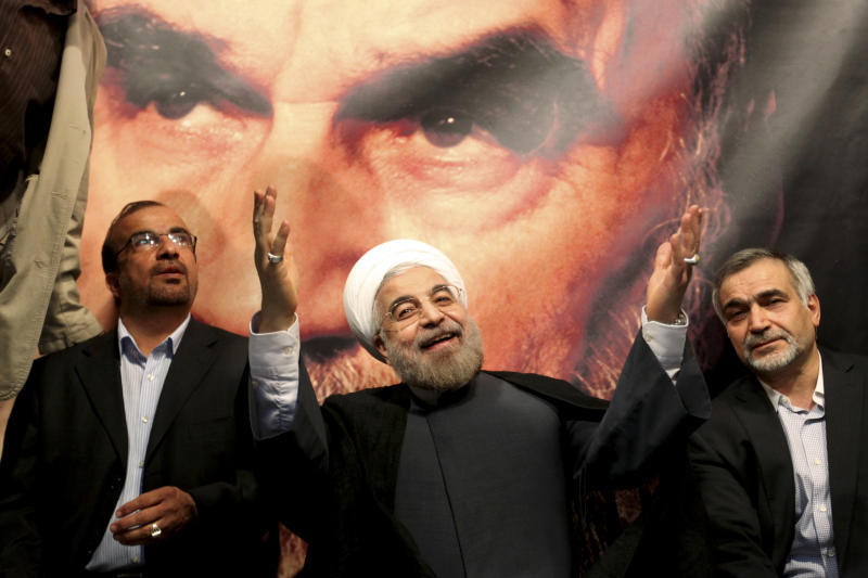 FILE - In this Saturday, June 1, 2013 file photo, in front of a portrait of the late Iranian revolutionary founder Ayatollah Khomeini, presidential candidate Hasan Rowhani, a former top nuclear negotiator, center, gestures to his supporters at a rally in Tehran, Iran. Iranian pro-reform candidate, Mohammad Reza Aref, pulled out of this week's presidential election to give support to a centrist whose campaign has gained momentum in recent days. The decision by Aref is seen as a major boost for Hasan Rowhani, who now faces off against five conservative candidates Friday. (AP Photo/Ebrahim Noroozi, File)