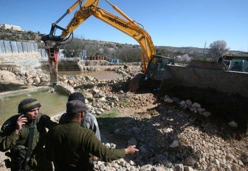 A man talks to Israeli soldiers as a bulldozer demolishes a water well used to irrigate agricultural land