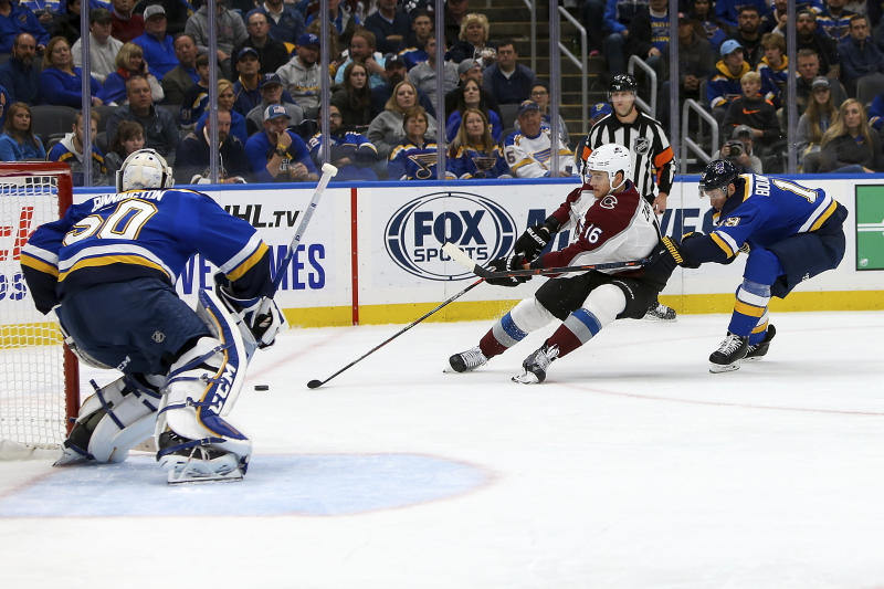 Colorado Avalanche's Nikita Zadorov (16), of Russia, handles the puck in front of St. Louis Blues' Jay Bouwmeester (19) as goaltender Jordan Binnington (50) protects the goal during the second period of an NHL hockey game Monday, Oct. 21, 2019, in St. Louis. (AP Photo/Scott Kane)