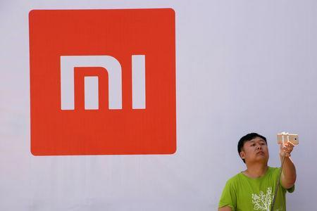 A man takes a selfie in front of the logo of Xiaomi at a venue for the launch ceremony of Xiaomi's new smart phone Mi Max in Beijing, May 10, 2016. REUTERS/Kim Kyung-Hoon/File Photo