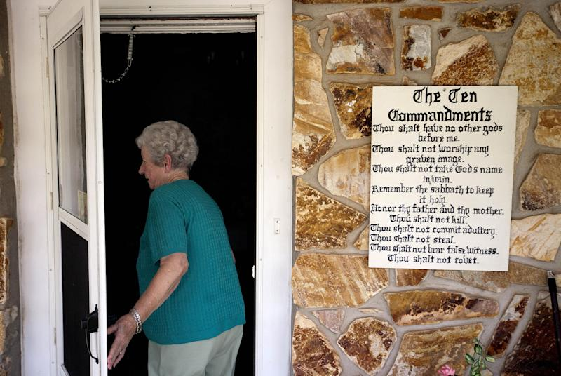 In this Tuesday, July 9, 2013 photo, Francis Carney steps into her house past the Ten Commandments hanging next to her front door, in Nelson, Ga. As the national debate over gun control swirled in the spring, the tiny Georgia city made a statement supporting gun rights by passing an ordinance requiring gun ownership. Now a national gun control group is using a lawsuit challenging that law to send a message of its own. (AP Photo/David Goldman)