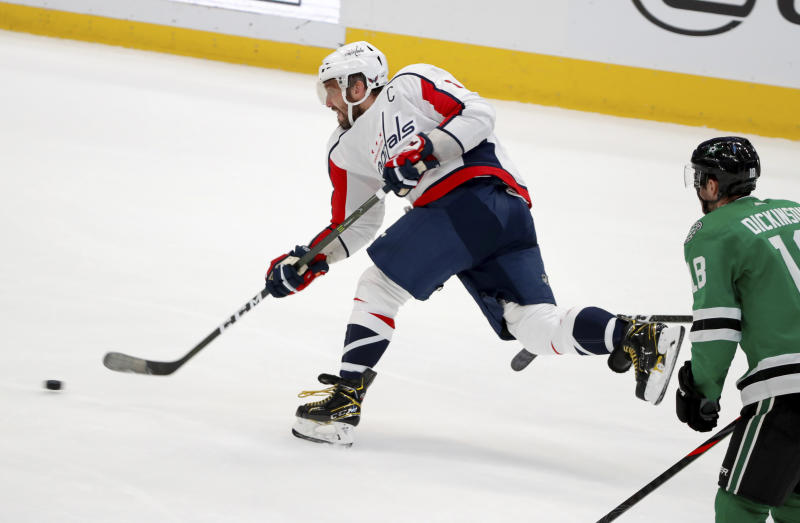 Washington Capitals left wing Alex Ovechkin (8) takes a shot in the closing seconds of the second period of an NHL hockey game as Dallas Stars center Jason Dickinson (18) looks on in Dallas, Saturday, Oct. 12, 2019. (AP Photo/Tony Gutierrez)