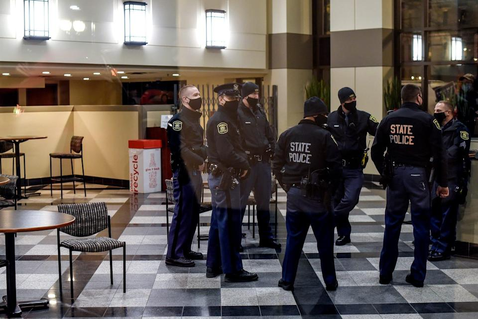 Michigan State Police wait in the lobby of the Anderson House Office Building while Rudy Giuliani testifies on election integrity during a Michigan House Oversight Committee hearing on Wednesday, Dec. 2, 2020, in Lansing.