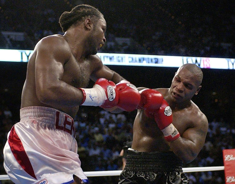 Lennox Lewis, left, goes after challenger Mike Tyson in the 8th round of their WBC/IBF heavyweight championship bout on June 8, 2002.