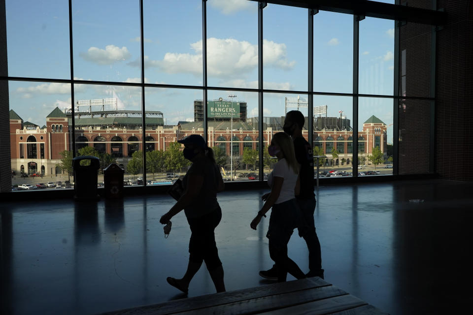 Globe Life Park, the former home of the Texas Rangers is visible through the windows of the of the new Globe Life Park as fans gather for Game 1 of the baseball World Series Series between the Los Angeles Dodgers and the Tampa Bay Rays Tuesday, Oct. 20, 2020, in Arlington, Texas. (AP Photo/Sue Ogrocki)