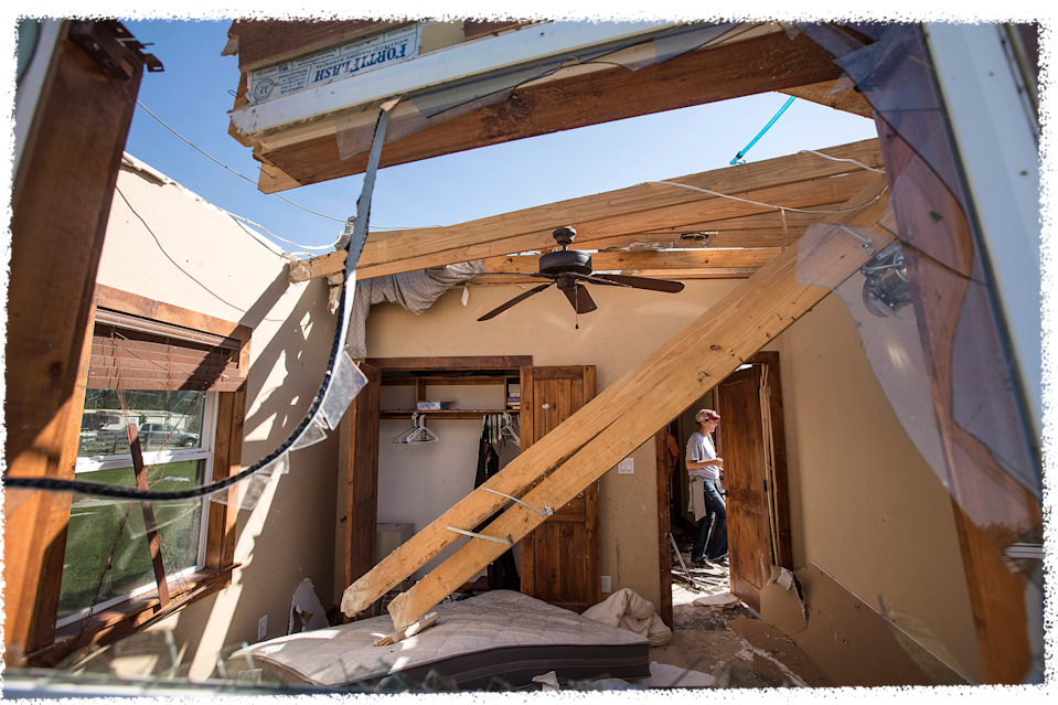 Robin Black walks past a doorway as she sifts through the rubble of her home after a tornado ripped through the area, Thursday, April 23, 2020, in Onalaska, Texas.