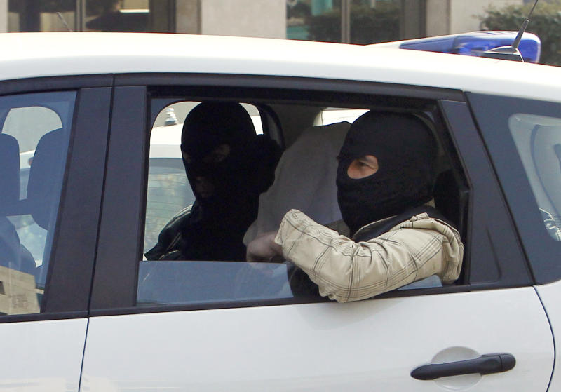 An unidentified man with his head covered, believed to be Abdelkader Merah or his companion, sits between masked police officers as they head to the French police's anti-terrorist headquarters in Levallois-Perret, outside Paris, Saturday, March 24, 2012. Merah's brother, Mohamed Merah is blamed for a series of deadly shootings which have shocked France and upended the country's presidential race. Merah, who claimed allegiance to al-Qaida, died in a hail of gunfire Thursday after a dramatic 32-hour-long standoff with law enforcement. (AP Photo/Christophe Ena)