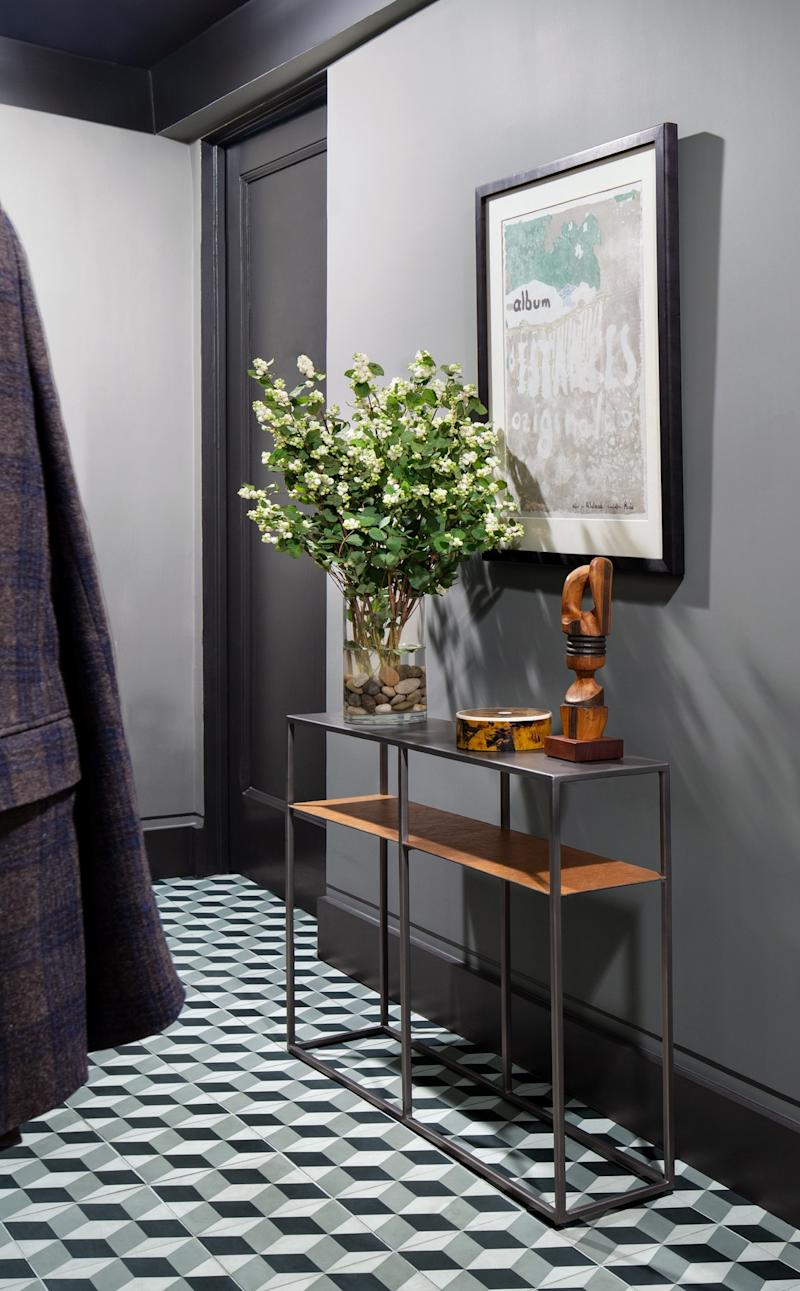 A Walker Zanger tile enlivens the entry, which is painted in Benjamin Moore's Rockport Gray. On the wall opposite the lithograph by Édouard Vuillard and a custom console table, designer Rabel transformed what was dead space into a pullout coat closet.