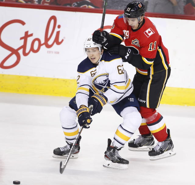 Buffalo Sabres' Brandon Montour, left, is knocked off the puck by Calgary Flames' Mikael Backlund during the third period of an NHL hockey game Thursday, Dec. 5, 2019, in Calgary, Alberta. (Larry MacDougal/The Canadian Press via AP)