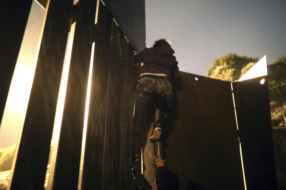 Honduran migrant Jennifer Ramos, 30, successfully climbs over a border barrier, in Tijuana, Mexico, Friday, Nov. 30, 2018. Ramos was detained by U.S. Border Patrol agents as soon after she stepped onto U.S. territory. Thousands of migrants who traveled via a caravan members want to seek asylum in the U.S. but may have to wait months because the U.S. government only processes about 100 of those cases a day at the San Ysidro border crossing in San Diego. (AP Photo/Felix Marquez)