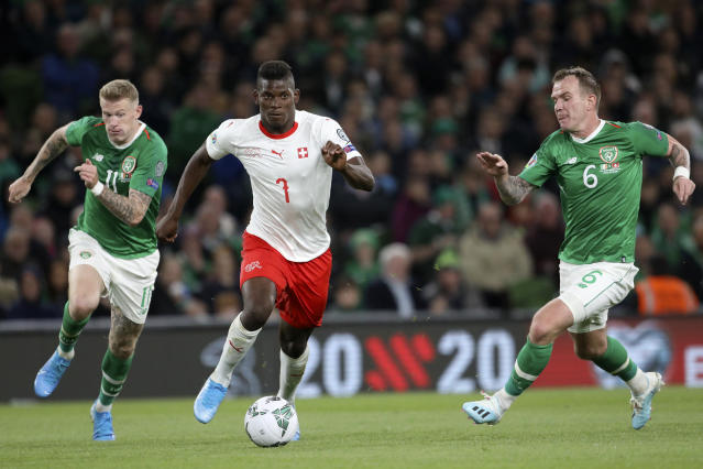 Switzerland's Breel Embolo runs with the ball between Ireland's James McClean and Glenn Whelan, right, during the Euro 2020 group D qualifying soccer match between Ireland and Switzerland at the Aviva stadium in Dublin, Thursday, Sept. 5, 2019. (AP Photo/Peter Morrison)