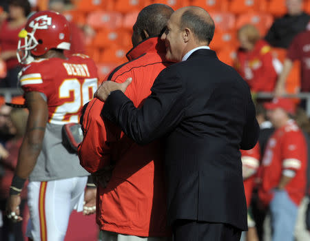 FILE PHOTO: Kansas City Chiefs head coach Romeo Crennel (L) is hugged by general manager Scott Pioli before the start of their NFL game against the Carolina Panthers December 2, 2012. Both men witnessed the suicide of linebacker Jovan Belcher the previous day. REUTERS/Dave Kaup (UNITED STATES - Tags: SPORT FOOTBALL)
