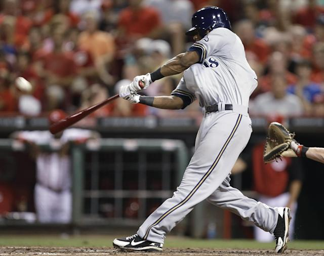 Milwaukee Brewers' Khris Davis hits a two-run home run off Cincinnati Reds relief pitcher Alfredo Simon in the eighth inning of a baseball game, Friday, Aug. 23, 2013, in Cincinnati. It was the second home run of the game for Davis. Milwaukee won 6-4. (AP Photo/Al Behrman)