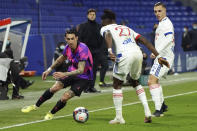 Paris Saint Germain's Angel Di Maria, left, challenges for the ball with Lyon' players during the French League One soccer match between Lyon and PSG in Decines, near Lyon, central France, Sunday, March 21, 2021. (AP Photo/Laurent Cipriani)