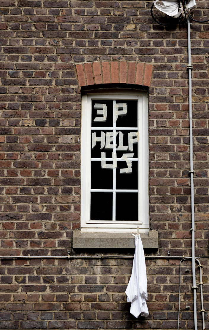 A sign is put up in a window with masking tape and a white cloth hangs outside after flooding in Trooz, Belgium, Tuesday, July 27, 2021. With electricity and gas cut off and communication lines damaged, the working-class neighborhood of La Brouck and its brick terraced houses looks like a ghost town. Since the water receded many have left to find shelter with friends while others have decided to stay. (AP Photo/Virginia Mayo)