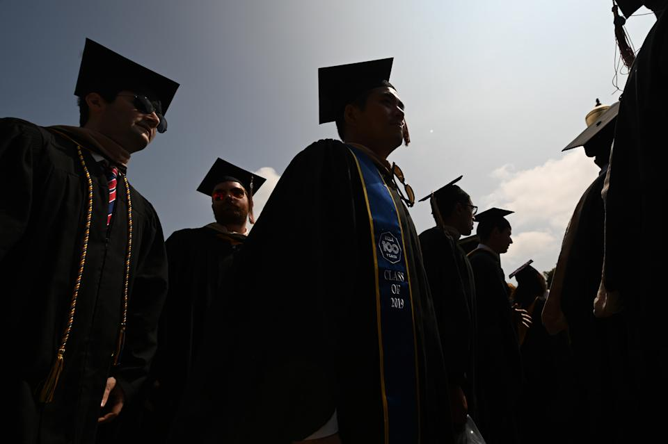 """Students wearing academic regalia attend their graduation ceremony at the University of California Los Angeles (UCLA), June 14, 2019 in Los Angeles California. - With 45 million borrowers owing $1.5 trillion, the student debt crisis in the United States has exploded in recent years and has become a key electoral issue in the run-up to the 2020 presidential elections. """"Somebody who graduates from a public university this year is expected to have over $35,000 in student loan debt on average,"""" said Cody Hounanian, program director of Student Debt Crisis, a California NGO that assists students and is fighting for reforms. (Photo by Robyn Beck / AFP)        (Photo credit should read ROBYN BECK/AFP/Getty Images)"""