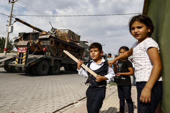 Children watch as army tanks are transported on trucks in the outskirts of border town Akcakale on Thursday (AP)
