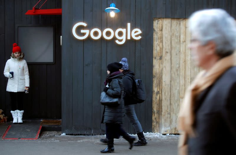 FILE PHOTO: People walk past the logo of Google in Davos