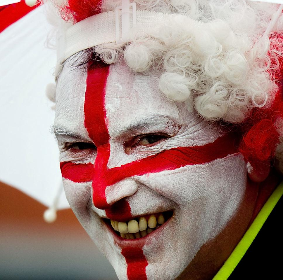 An English fan waits for the rain to stop during day four of the international cricket Test match between New Zealand and England played at the Basin Reserve in Wellington on March 17, 2013.   AFP PHOTO / Marty MELVILLE        (Photo credit should read Marty Melville/AFP/Getty Images)