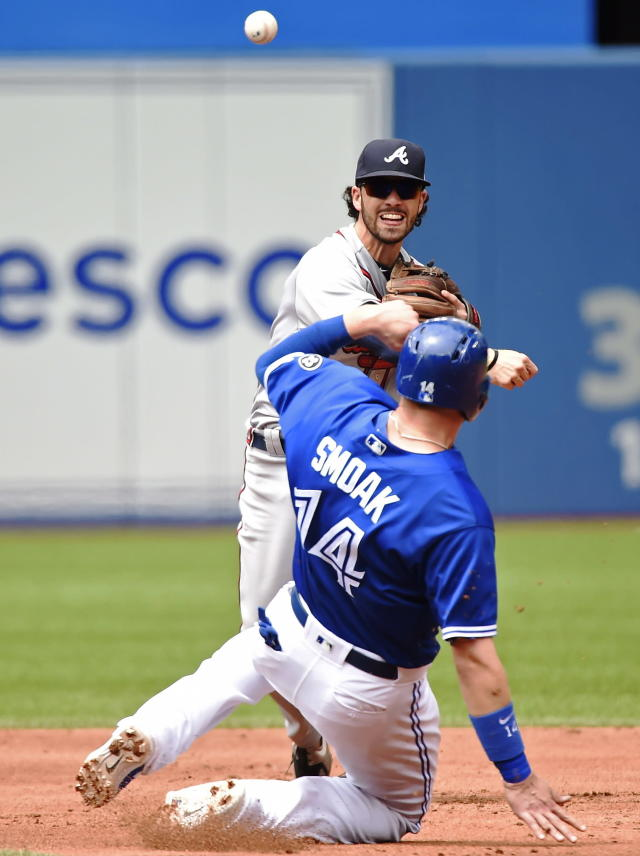 Atlanta Braves shortstop Dansby Swanson forces out Toronto Blue Jays first baseman Justin Smoak (14) at second base as he throws to first base to complete the double play on a ball hit by Toronto Blue Jays' Yangervis Solarte during the third inning of a baseball game in Toronto, Wednesday, June 20, 2018. (Nathan Denette/The Canadian Press via AP)