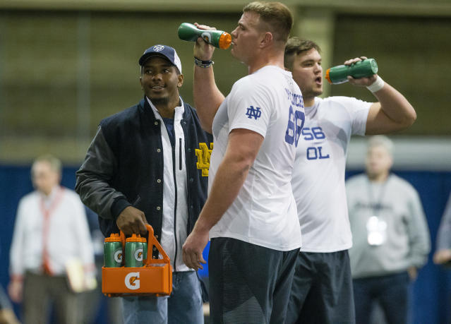 Quarterback Brandon Wimbush, left, makes sure Mike McGlinchey, center, and Quenton Nelson stay hydrated as they run drills during Notre Dame Pro Day football workouts in South Bend, Ind., Thursday, March 22, 2018. (Michael Caterina/South Bend Tribune via AP)
