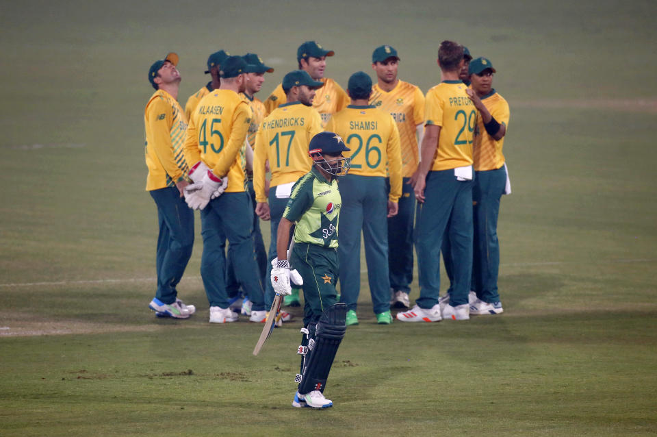 Pakistan's Babar Azam, center front, walks back to pavilion while South Africa players celebrate his dismissal during the 2nd Twenty20 cricket match between Pakistan and South Africa at the Gaddafi Stadium, in Lahore, Pakistan, Saturday, Feb. 13, 2021. (AP Photo/K.M. Chaudary)