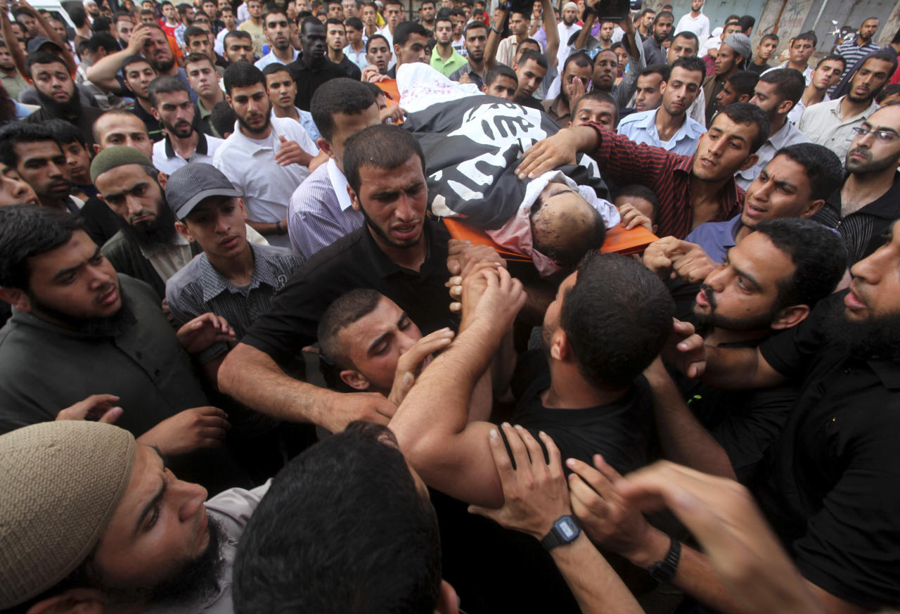 Palestinian mourners carry the body of militant Basil Ahmad during his funeral in Bureij refugee camp, central Gaza Strip, Friday, June 22, 2012. Palestinian sources say that Ahmad was killed during an Israeli airstrike east of Bureij refugee camp on Friday. An Israeli airstrike killed a Gaza militant Friday as he was preparing to launch rockets, Israel's military said, the latest casualty in a week-long exchange of cross-border attacks. (AP Photo/Ashraf Amra)