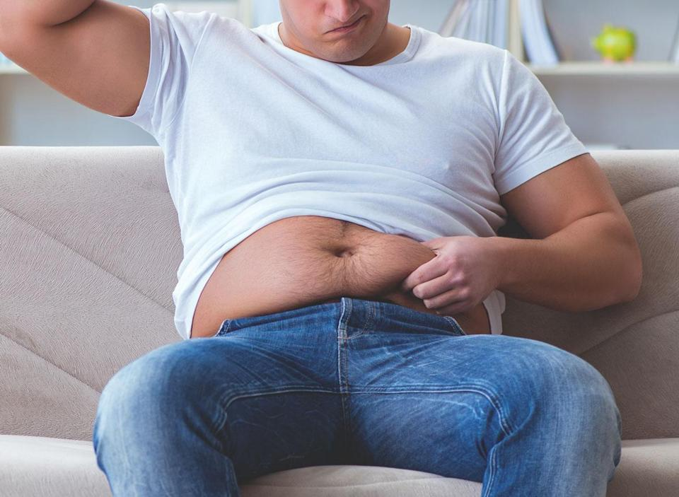 Man upset and questioning belly fat as he grabs stomach
